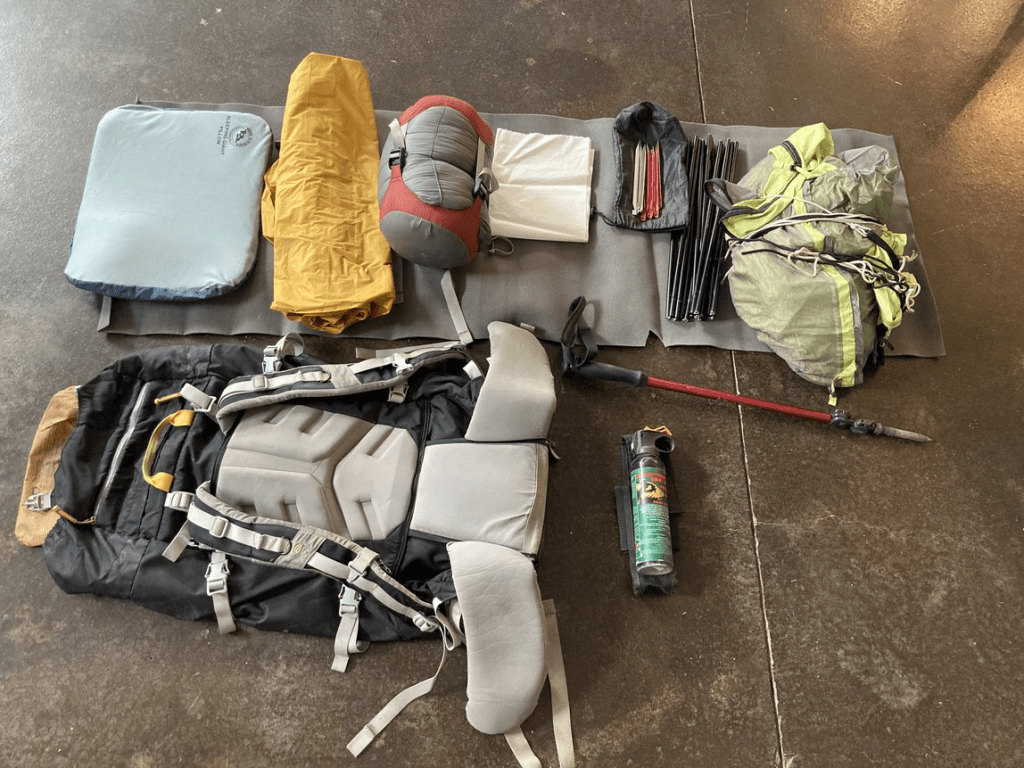 backpack, sleeping pad, sleeping bag, tent and other camp supplies laid out on the ground.