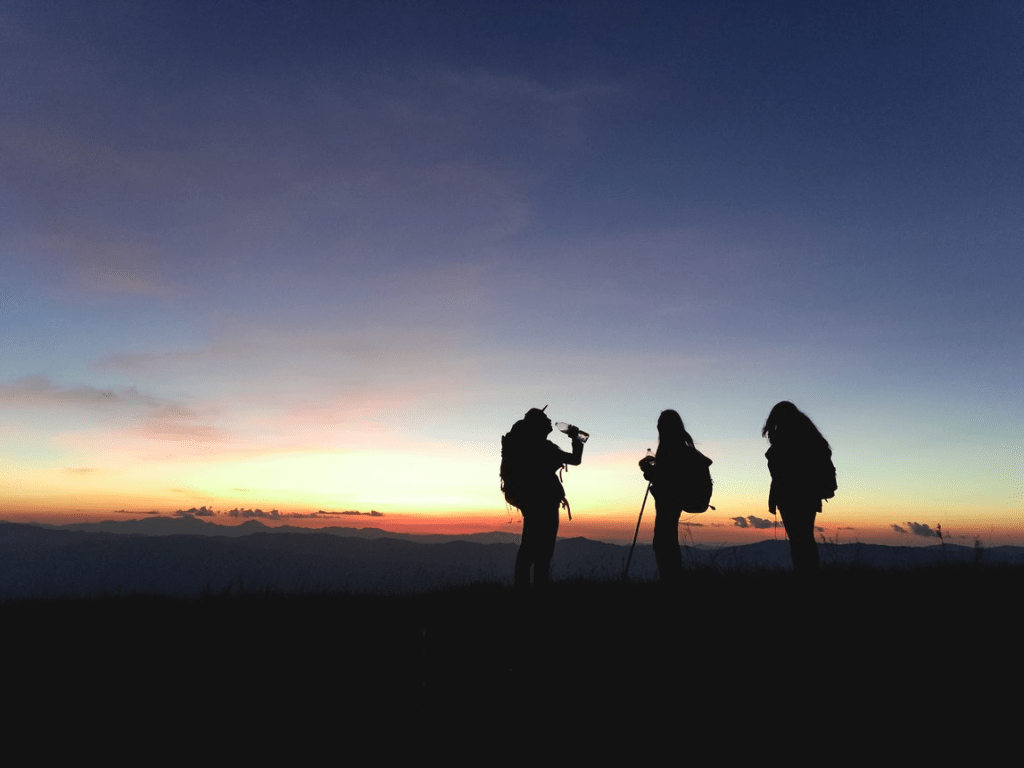 three hiker silhouettes on a summit during sunset