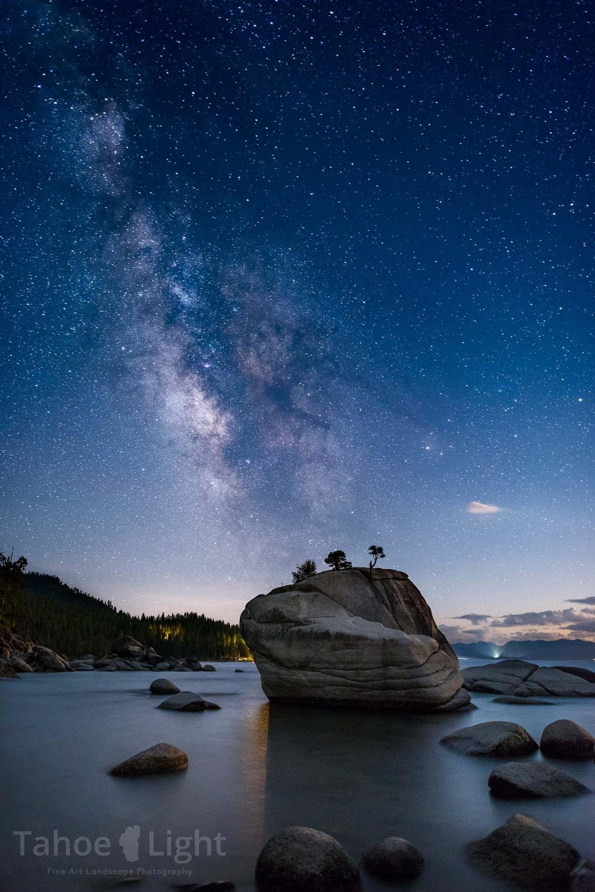 A night sky with stars and the Milky Way in the distance and a rock island in the foreground.