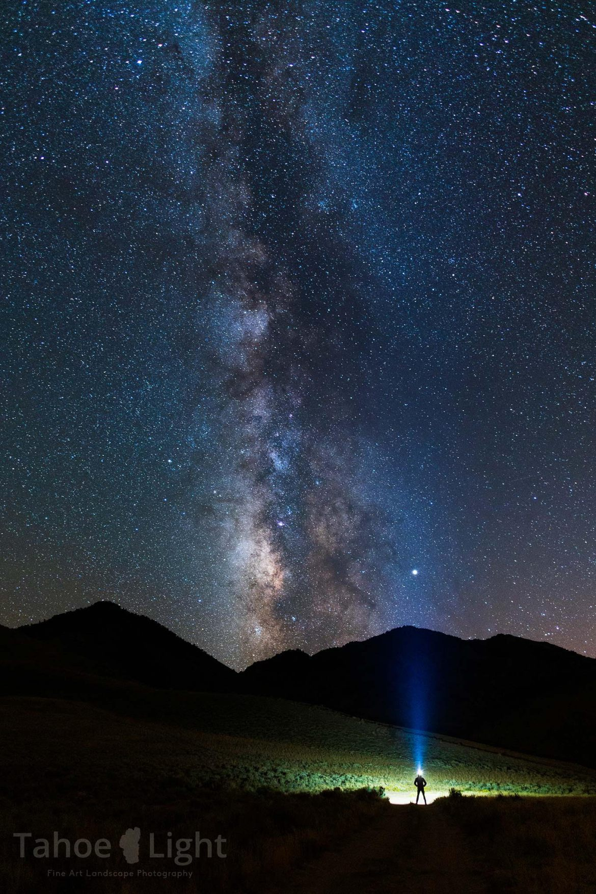 The Milky Way stretches across the night sky with a person with a bright headlamp standing with hands on hips in front of mountain.