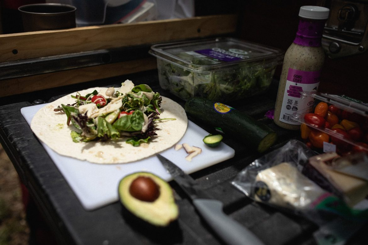 An open tortilla sits on a cutting board, topped with spring mix, halved cherry tomatoes, and salad dressing. A halved avocado, a cucumber, and some cheese also sit on the table.