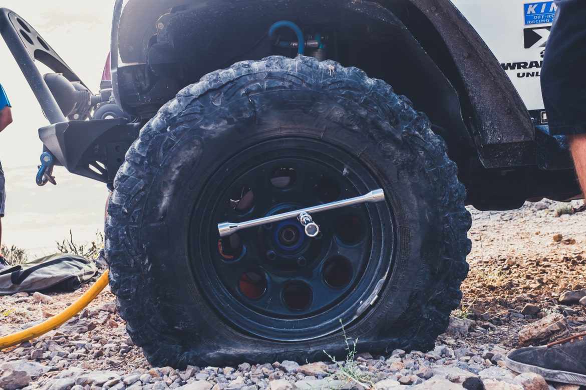 A close-up of vehicle shows a flat tire with a torque wrench wedged in the hub.