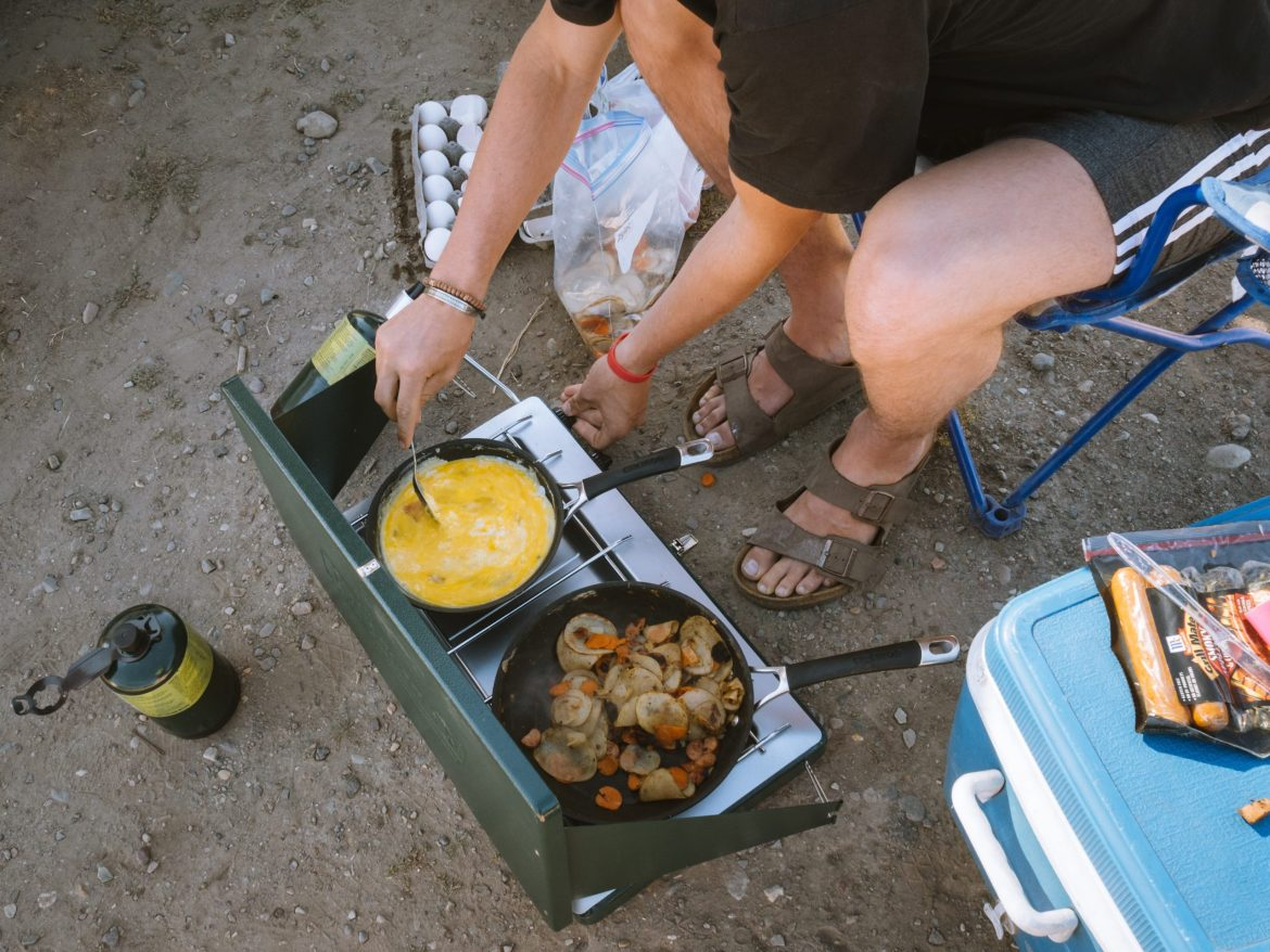 An overlander sits in a camping chair, tending to scrambled eggs in a skillet on a two-burner portable stove. Vegetables sauté in the a pan on the other skillet. A pack of sausages sit on a cooler in the foreground.