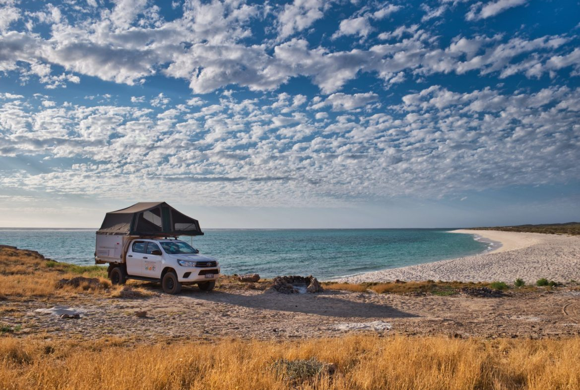 A modified truck with a storage unit in the back and a rooftop tent is parked at a beach on a sunny day. Turquoise water laps behind and stratocumulus clouds cover the blue sky.