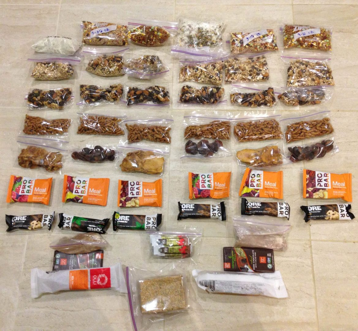 Six days worth backpacking food lies in rows on the floor. Dehydrated meals, trail mix, and dried fruit have been repackaged into small ziplock pages. The allotment also contains bars, instant coffee, and two bars of chocolate.