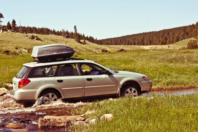 A Subaru Outback negotiates a stream running through a field.