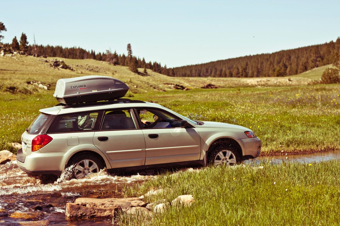 A Subaru Outback negotiates a stream running through a field.
