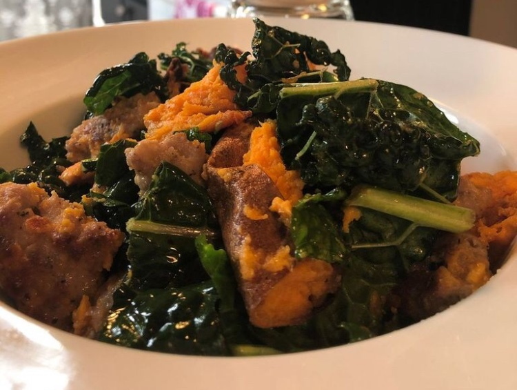 A close up shows a bowl of roasted sweet potatoes, sausage, and kale.