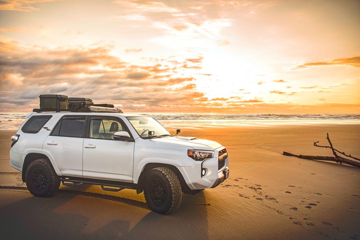 An SUV with a roof rack is parked on a beach at sunset.