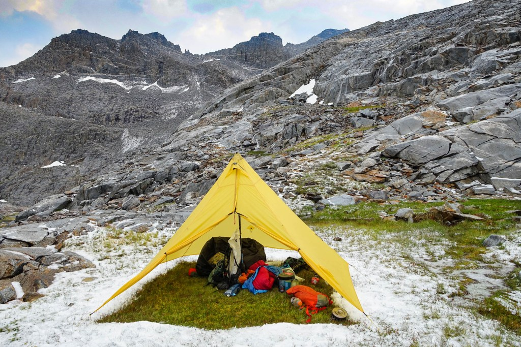 A tarp tent filled with backpacking gear sits on a snowy, grassy outcropping on a rocky mountainside.