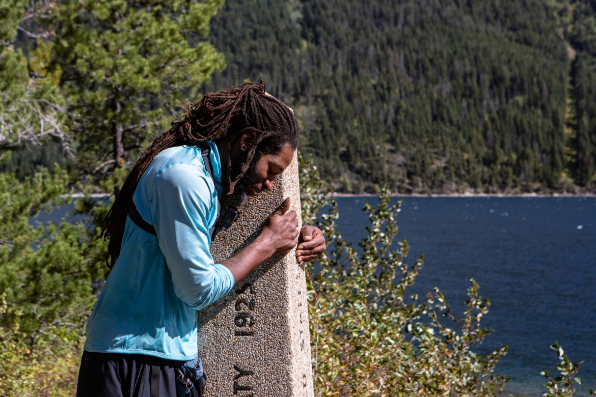 Akuna hugs a pole signifying the US/Canadian border and also the end of the PCT.