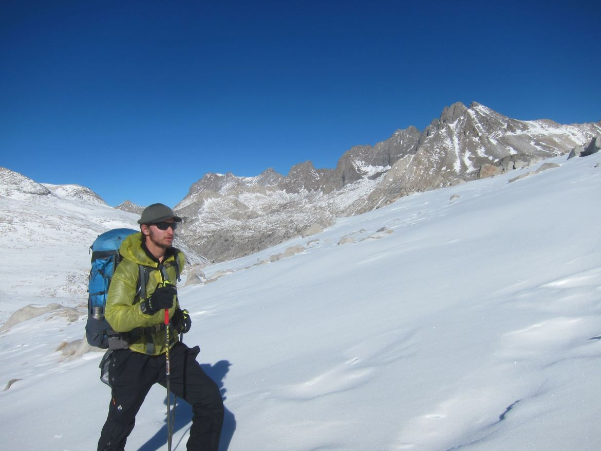 Lichter backcountry skis up a mountain. He has a a full backpacking pack on his back, and craggy mountains jut into the bluebird sky behind him.