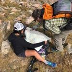 Two people pour over a paper map in the backcountry.