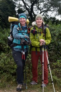 Fidgit and Neon smile for the camera while carrying their backpacking packs and trekking poles. They are standing in front of a forest.