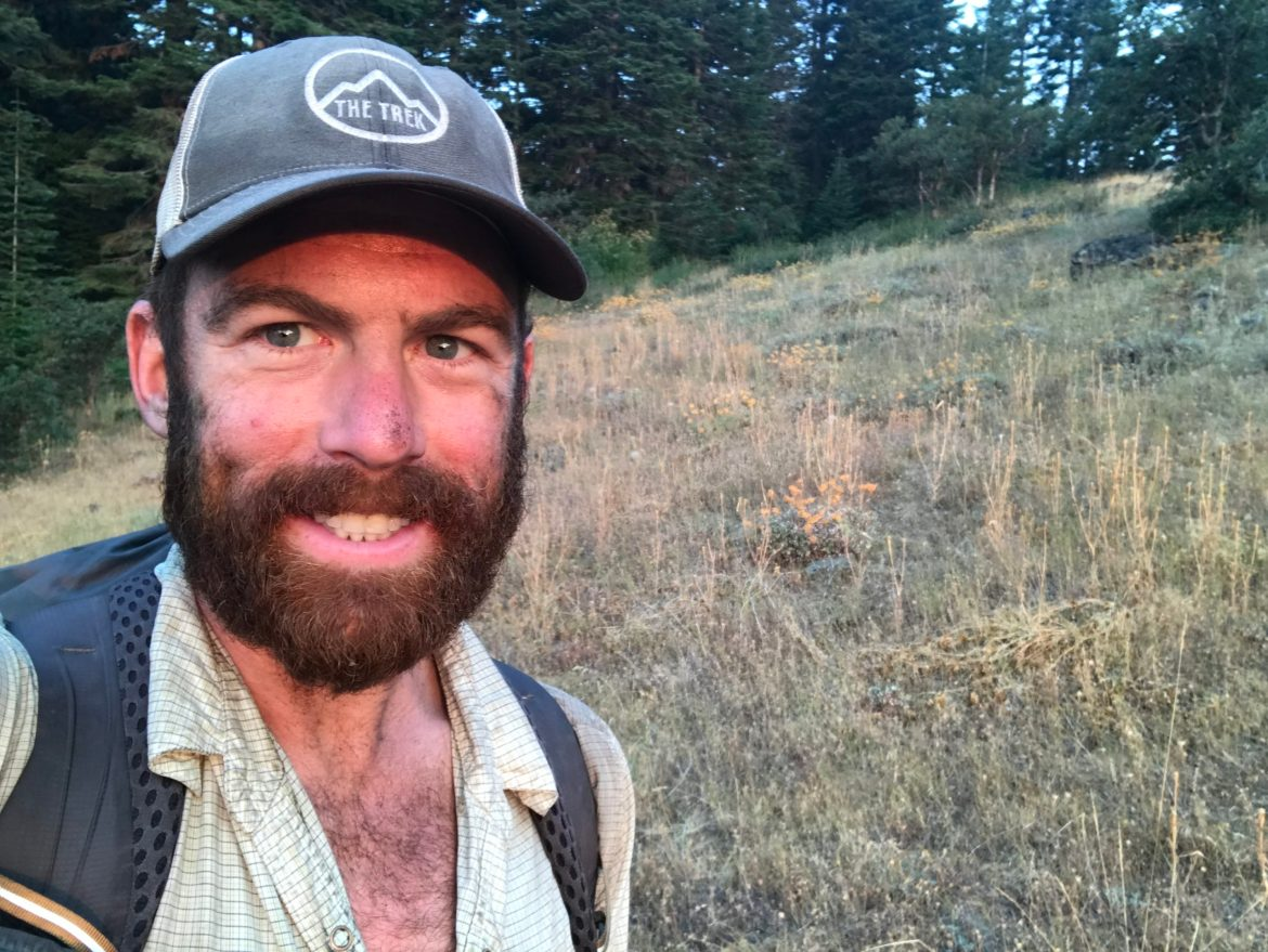 "Zach ""Badger"" Davis smiles for the camera. He's wearing a baseball cap and a backpack, and is standing in a field."