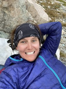 Mary smiles while lying down with her head on a rock.
