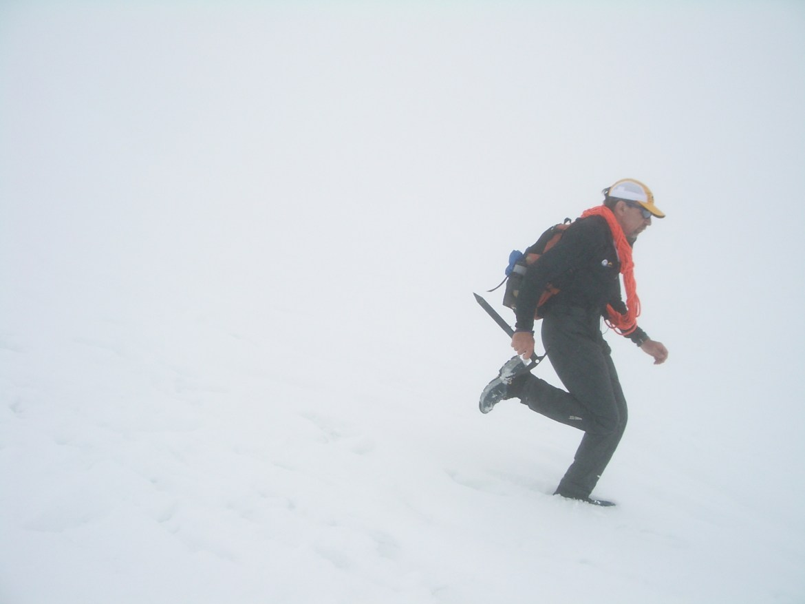 Buzz Burrell runs down a snowfield on Mt. Rainier in a white-out. He's carrying an ice axe and shouldering a cord of rope.
