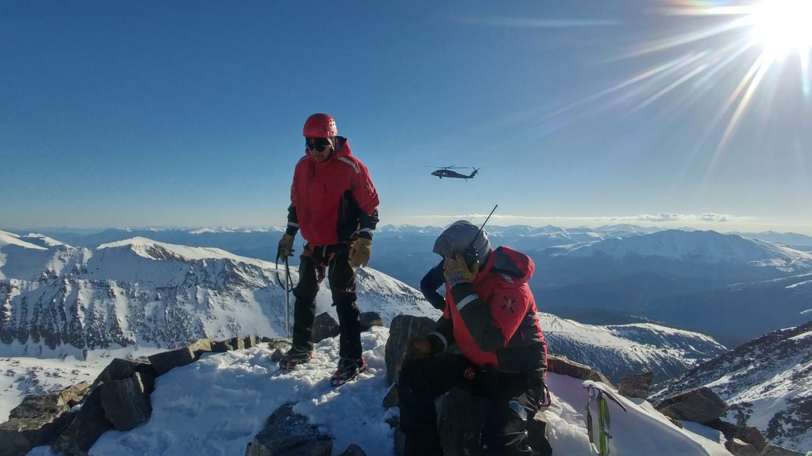 Two members of search and rescue wait on a mountain summit. A helicopter is flying above more peaks behind them.