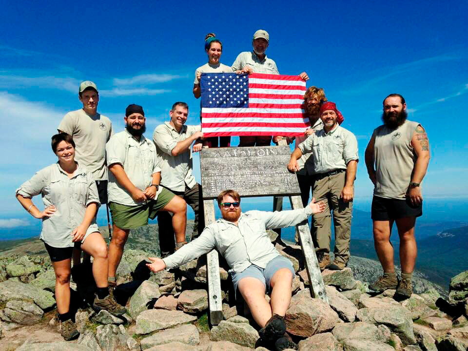 A Warrior Expeditions group stands on top of Mount Katahdin. They are posing and smiling around the sign, and two people are holding an American flag.