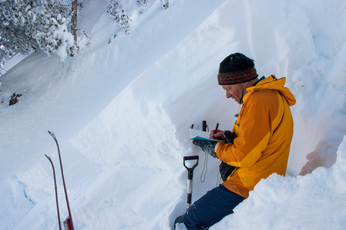 Bruce Tremper writes in a notebook in a snow put. The tips of his skis and a shovel handle are visible on the bottom of the image.