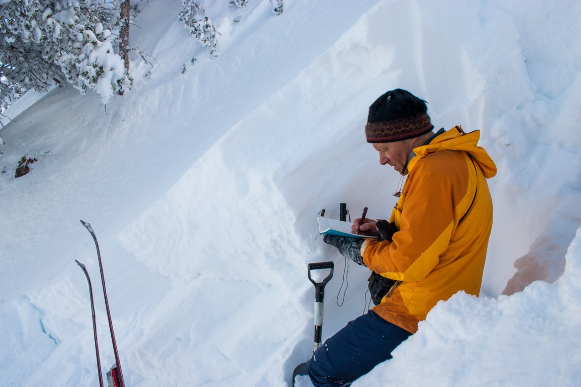 Bruce writes in a notebook while examining the snowpack in a deep snowfield. His shovel and skis are just visible in the bottom of the photo.