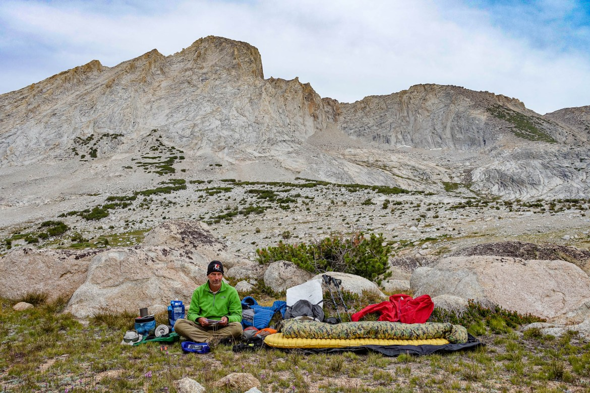 Adventure Alan sits with all of his backpacking gear spread out around him in front of some barren peaks.