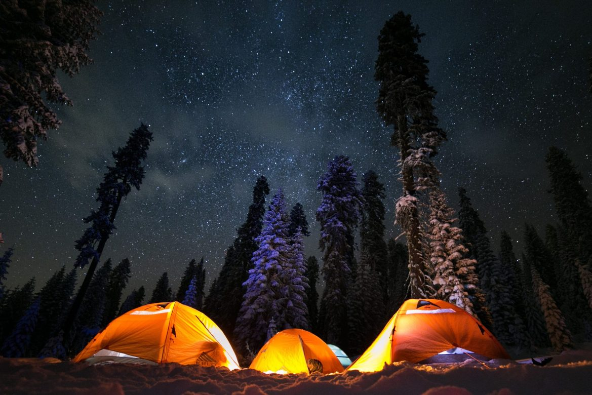 Three tents sit in the snow, surrounded by snow-covered trees and a sky full of stars overhead.