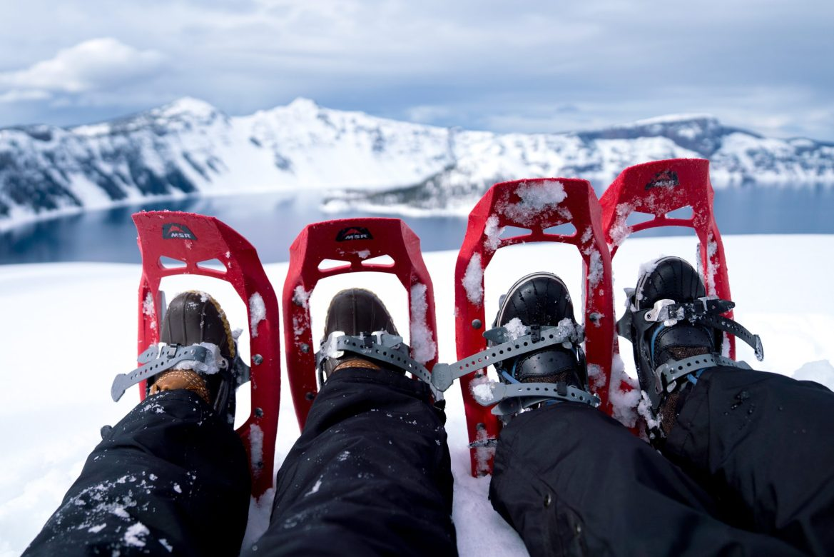 Two pairs of feet in snow shoes lying on the snow, with a lake and snow-capped peaks in the distance.