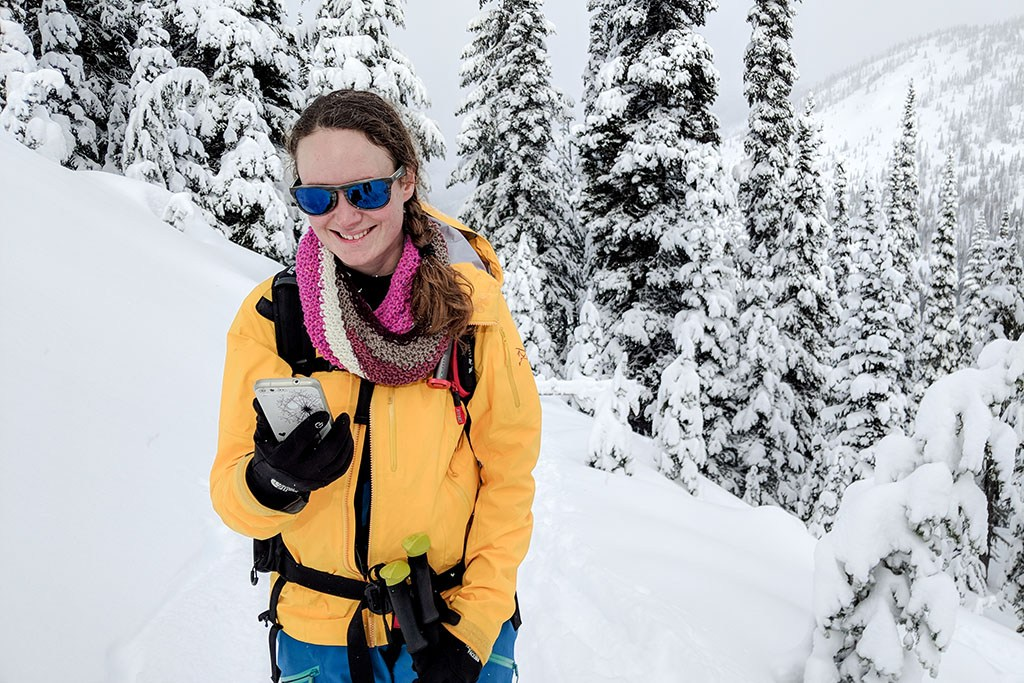 A backcountry skier smiles while looking at her phone. She stands in front of a row of snow-covered coniferous trees.