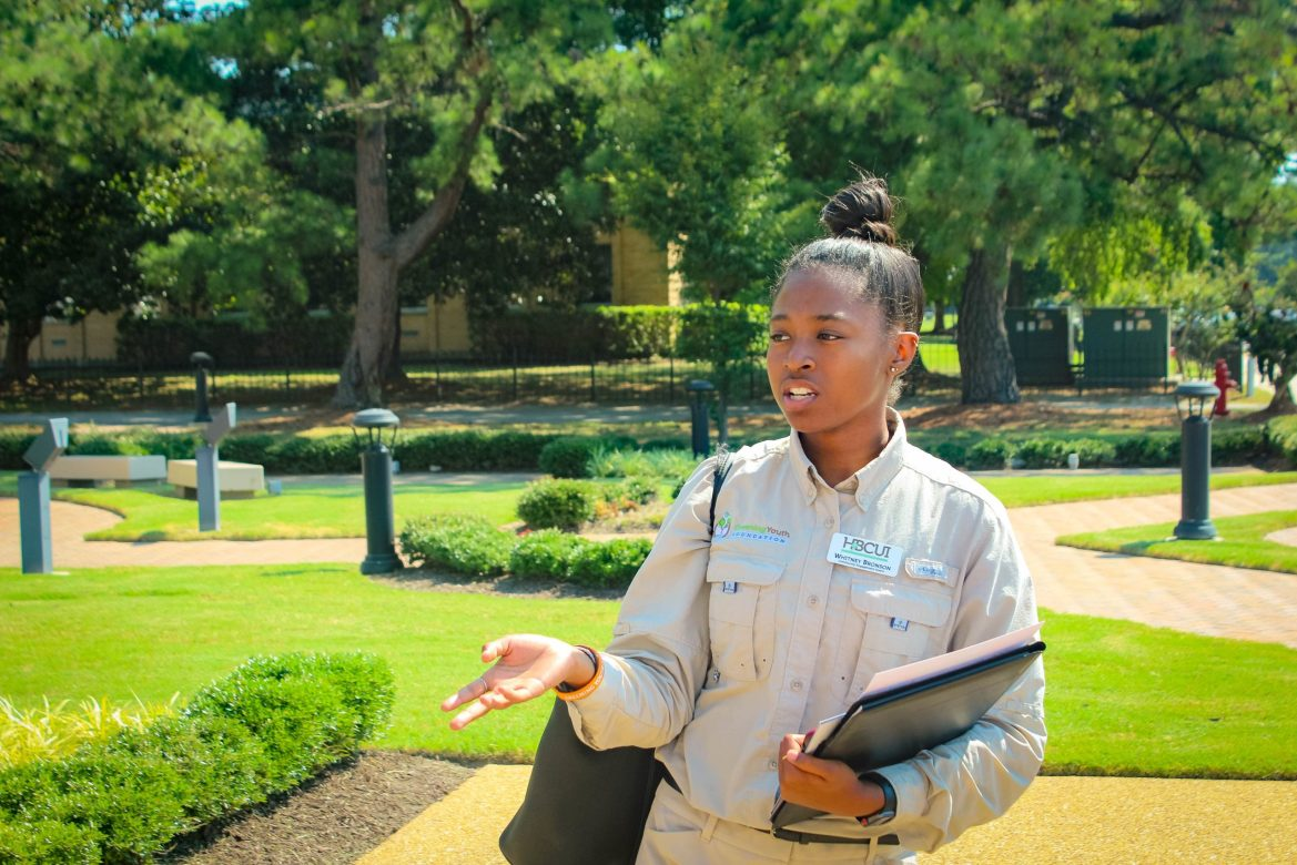 A GYF intern holds a clipboard in one hand and extends her other hand out. She stands in a sunny, manicured grassy park.
