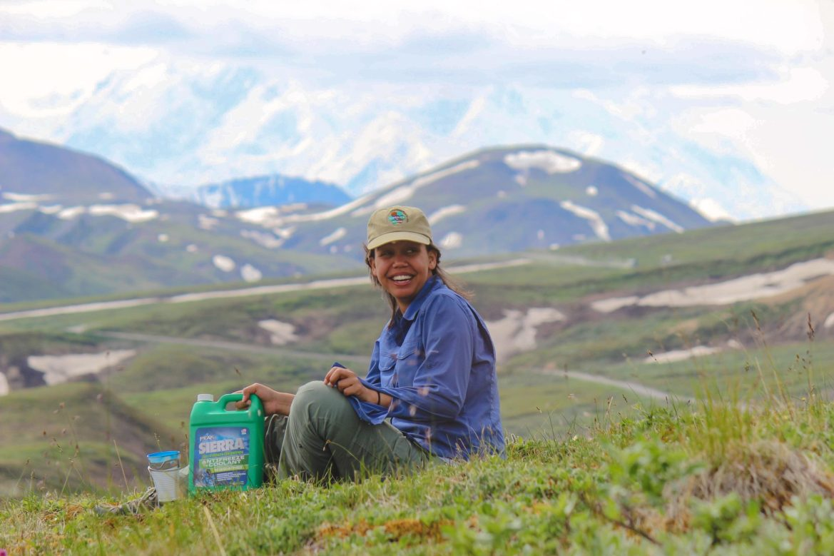 A GYF intern smiles while sitting in a field and holding a bottle of anti-freeze. Snowcapped peaks rise into a cloudy sky behind her.