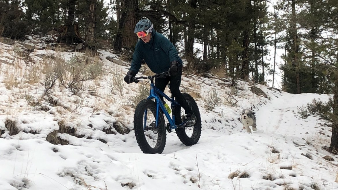 A fat biker rides over a snowy trail with a small dog running behind.