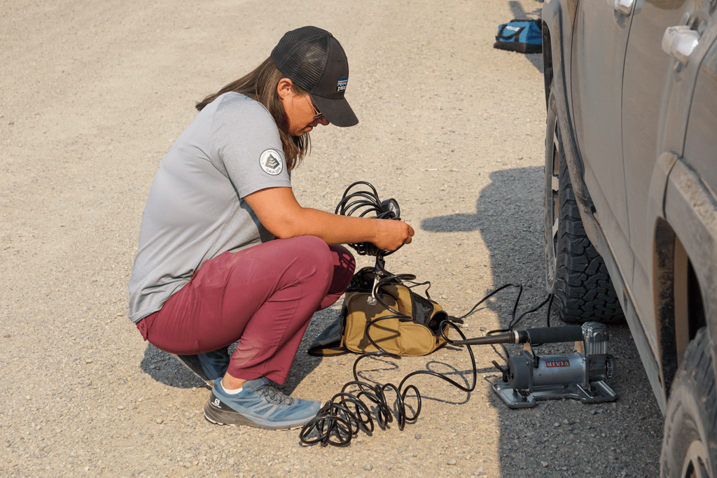 Person kneeling next to vehicle managing the air tubes for a compressor in order to put air back into the tires.