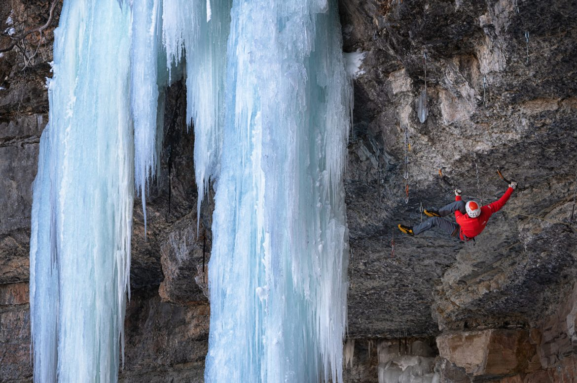 An ice climber hangs from an overhanging rock wall with a frozen waterfall beside him.
