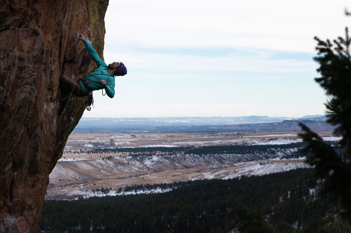 Segal is hanging onto a rock wall with one hand. His feet are placed on the rock below, and his other hand is pulling the rope attaching him to the wall up to clip it in higher. Snowy plains extend behind.