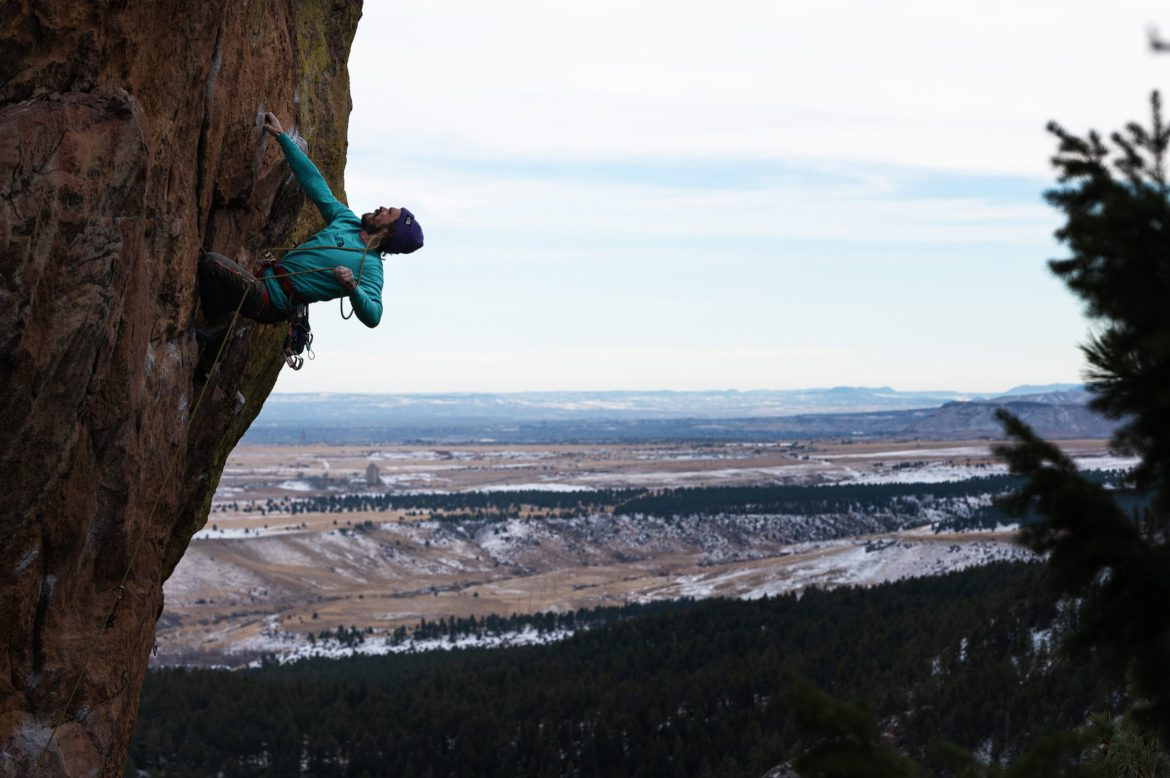 Matt hangs from a rock wall with the snowy Colorado plains in the background. He's lead climbing the route, with one hand hanging onto the wall and the other hand holding the rope.