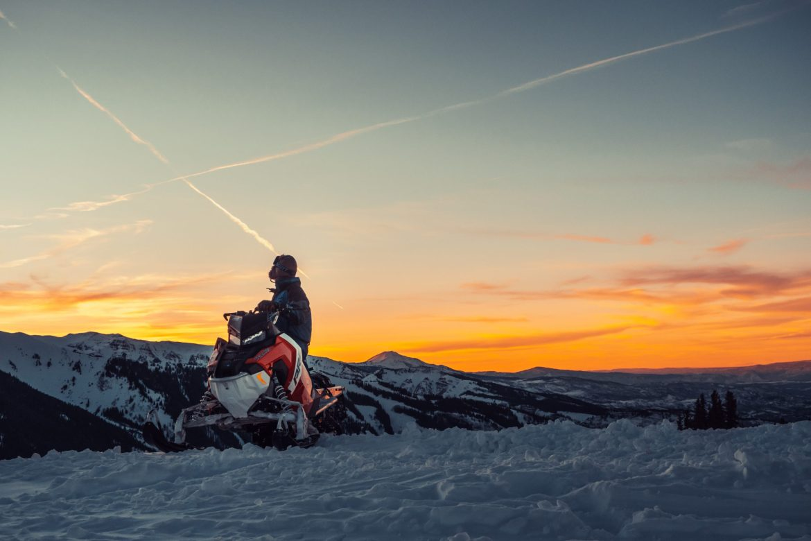 A snowmobiler looks off at the sunset over the mountains.