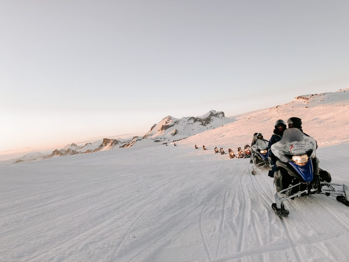 A single file line of sledders ride over a snowy plain with small mountains in the distance.
