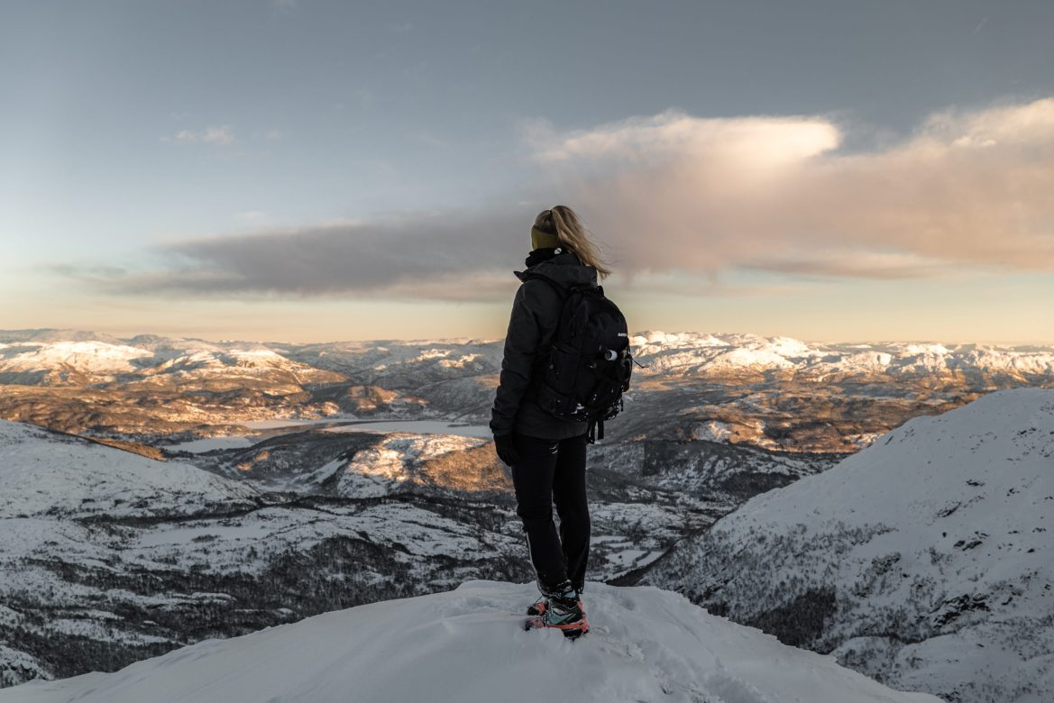 A hiker stands with their back to the camera, gazing down from the top of a mountain onto mountains, a lake, and plains covered in snow. They're wearing a headband, winter coat, and a backpack.