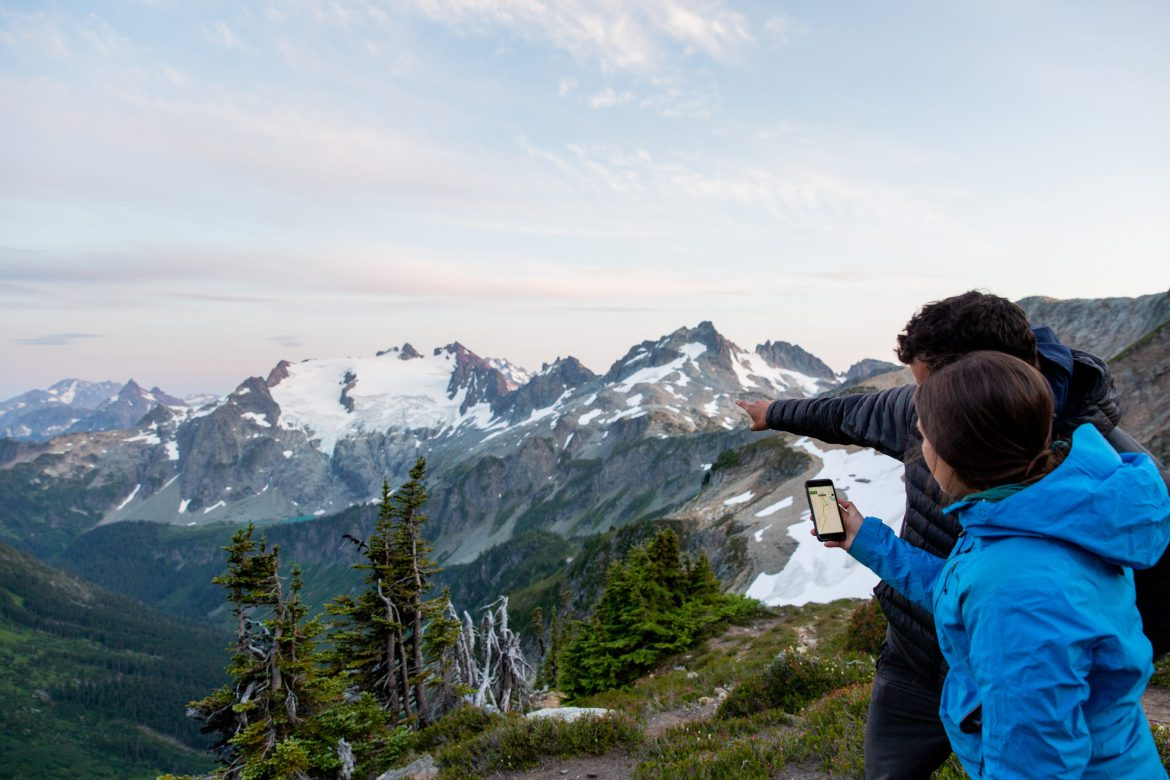 Two people look at Gaia on their phone while gazing at mountains in the background.