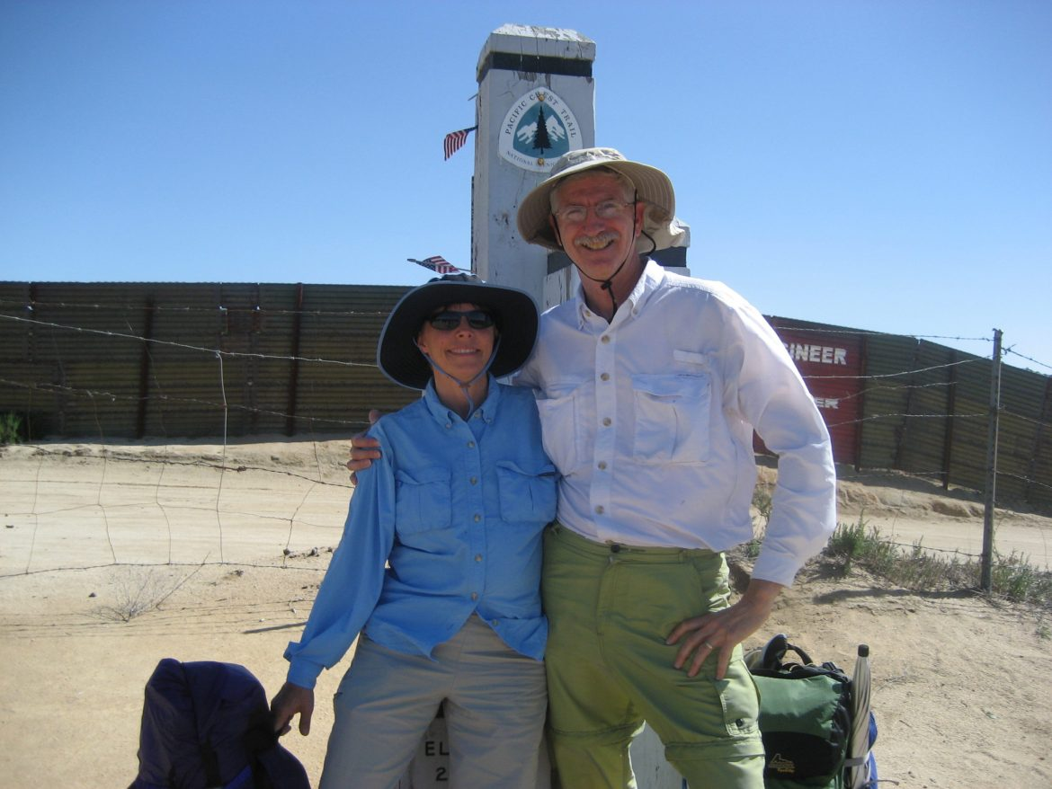 Scout and his wife Sandy stand in front of a sign post for the southern terminus of the PCT. They have their arms around each other and are smiling.