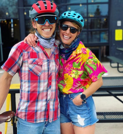 Phoebe and Ian smile with their arms around each other. They're wearing helmets, sunglasses, and button-down short-sleeved shirts and jorts. Ian has his hand on a bicycle saddle.
