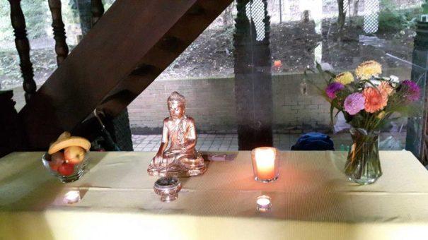 """Die golden glänzende, hauseigene Buddha-Staue haben wir aus ihrem dunklen Koffer befreit und ihr den schönsten Platz zugewiesen. Davor noch ein Räucherstäbchen, für das """"buddhistische Flair"""" und Früchte und Blumen als symbolische Opfergaben."""