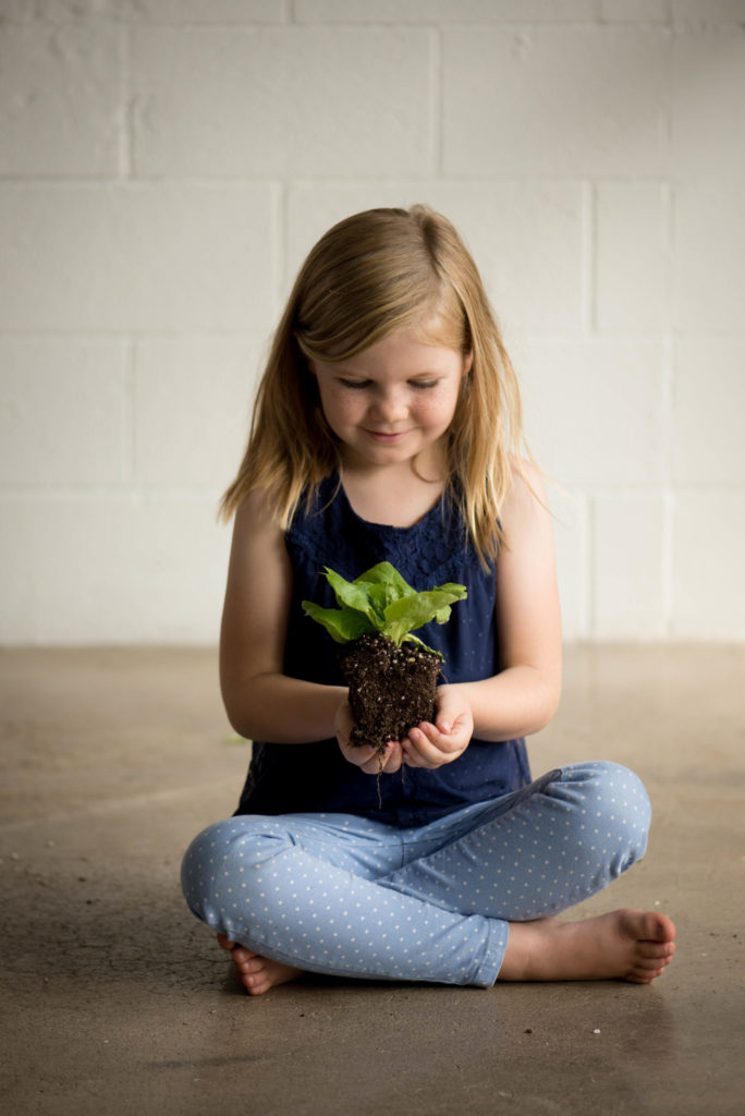 young girl touching dirt