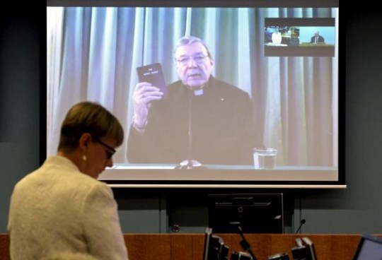 Senior Counsel Assisting Gail Furness stands in front of a screen displaying Australian Cardinal George Pell as he holds a bible while appearing via video link from a hotel in Rome, Italy to testify at the Australia's Royal Commission into Institutional Response to Child Sexual Abuse in Sydney, Australia, February 29, 2016.