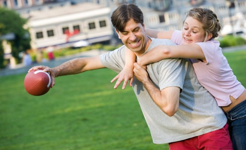 Playful couple playing football in park