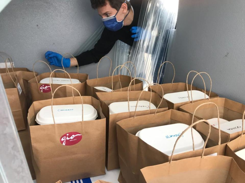 Riccardo, the son of the owner of GIO Gelati, carefully selecting the next delivery bag from the refrigerated van.