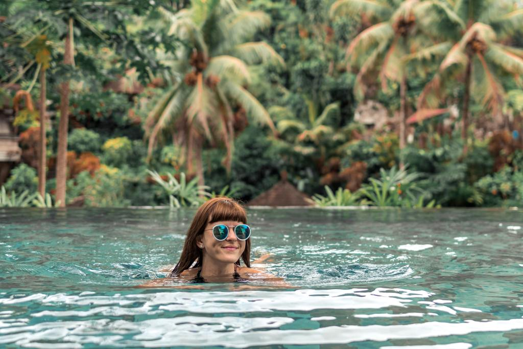 Woman swimming beside tropical palm forest