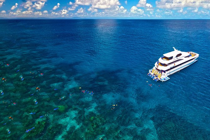 People diving and snorkeling near a yacht on a Great Barrier Reef diving and snorkeling tour from Cairns, Australia