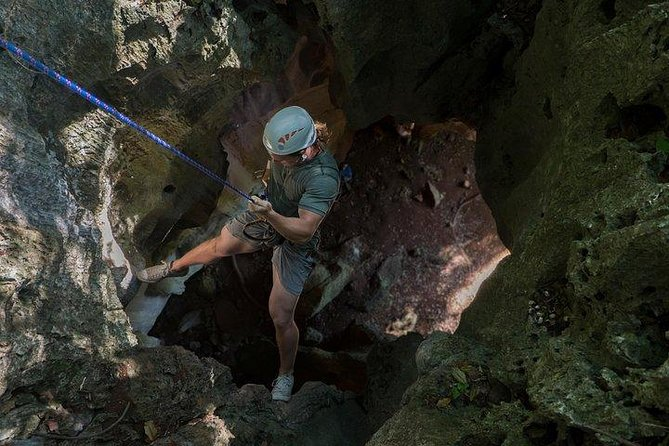 A man abseiling down a cave.